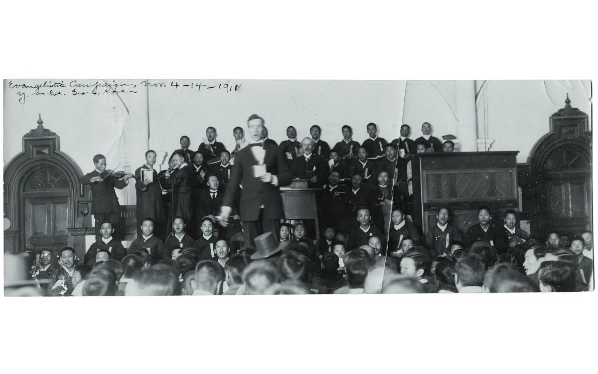 YMCA의 집회 모습(1911). 집회에서 악기 반주에 맞추어 노래를 부르고 있다.<br />단상에 앉은 언더우드 옆으로 이승만의 모습이 보인다.